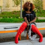 Katarra Parson sitting on curb outside in Grand Center